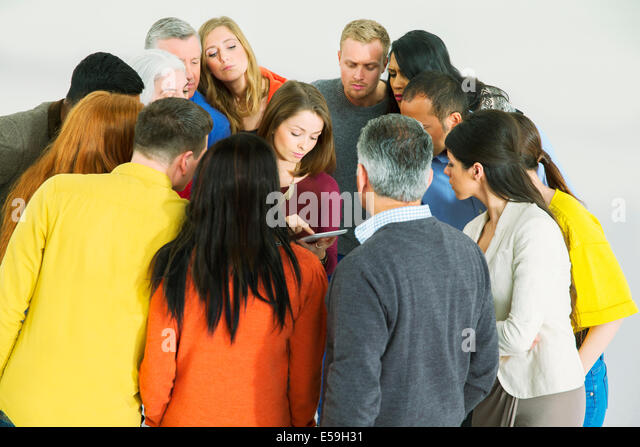 Business people huddled around businesswoman with laptop - Stock-Bilder