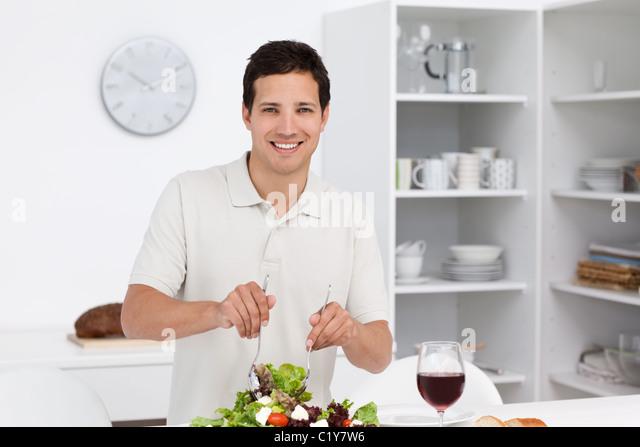 Happy man preparing a salad while drinking red wine - Stock-Bilder