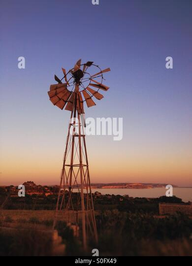 Windmill on Gozo, Malta with Comino in background - at sunset. - Stock Image
