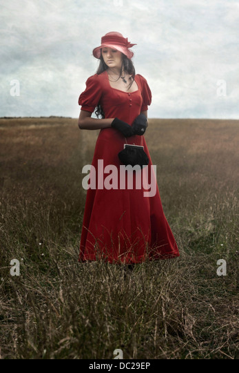 a woman in a red dress is standing on a field - Stock Image