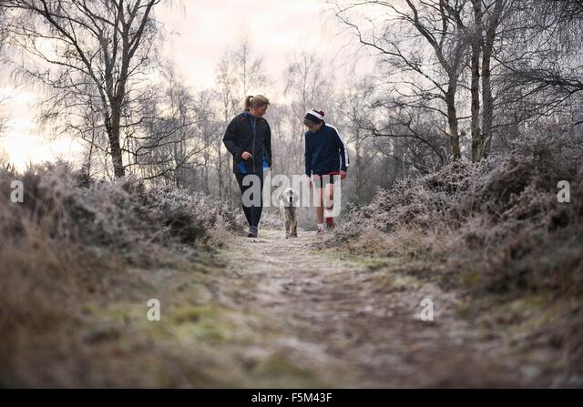 Front view of mother and son walking with dog looking down - Stock Image