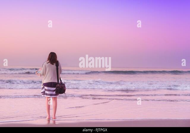 Rear View Of Woman Standing On Shore At Beach Against Sky - Stock Image