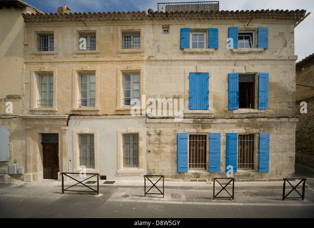 Two adjoining old stone 3-storey houses in Arles, France, one with blue shutters on the windows - Stock Image