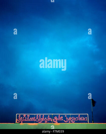 An Arabic neon sign over the Constitutional Democratic Party Headquarters in Tataouine , Tunisia. - Stock Image