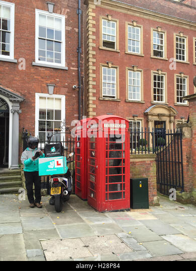 Male Deliveroo bike rider delivery driver delivering, on Low Pavement. Nottingham. - Stock Image