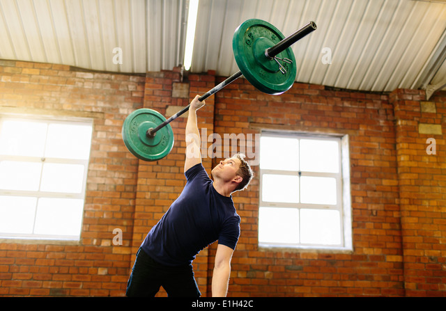 Man lifting barbell with one hand - Stock Image