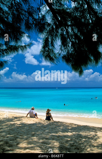 West Bay Beach Grand Cayman Island families swimming relaxing on deserted beach - Stock Image