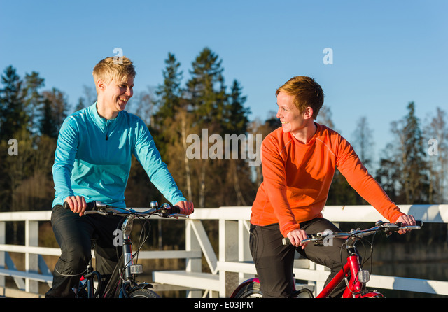 Two women cycling together along the bridge at sunrise - Stock Image