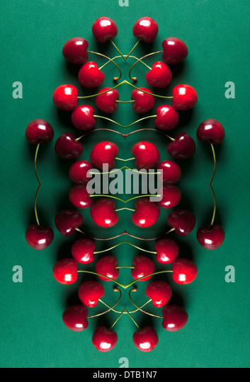 A digital composite of mirrored images of an arrangement of cherries - Stock Image