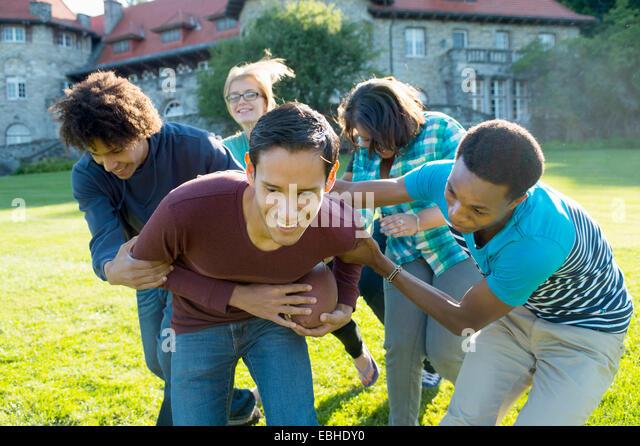 Students playing American football - Stock-Bilder