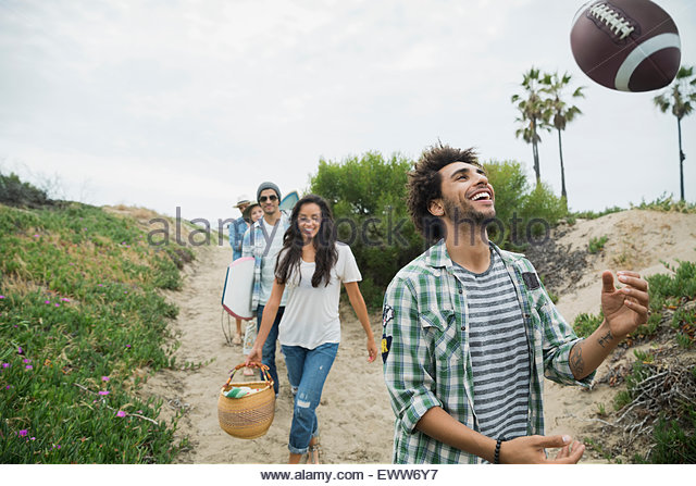 Smiling young man throwing football on beach path - Stock Image