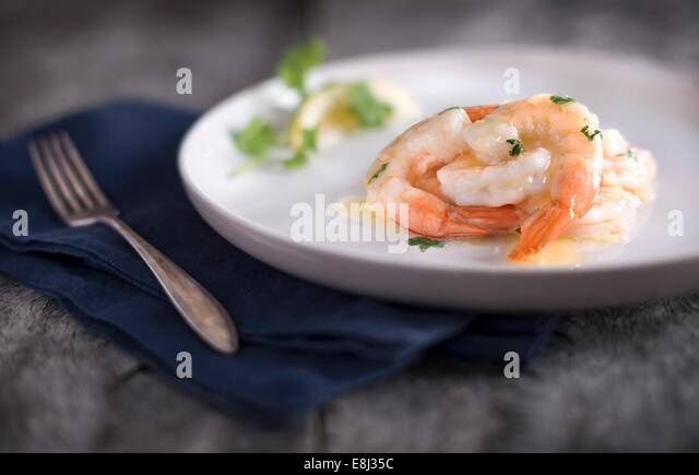 Plated shrimp with butter and herb sauce. Placed on a rustic gray wood surface with blue linen and antique fork. - Stock Image