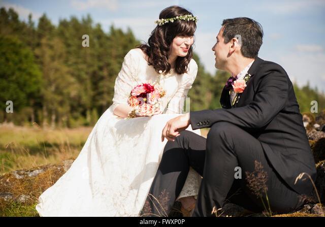 Sweden, Smaland, Vetlanda, Holsbybrunn, Newlyweds face to face in field - Stock Image