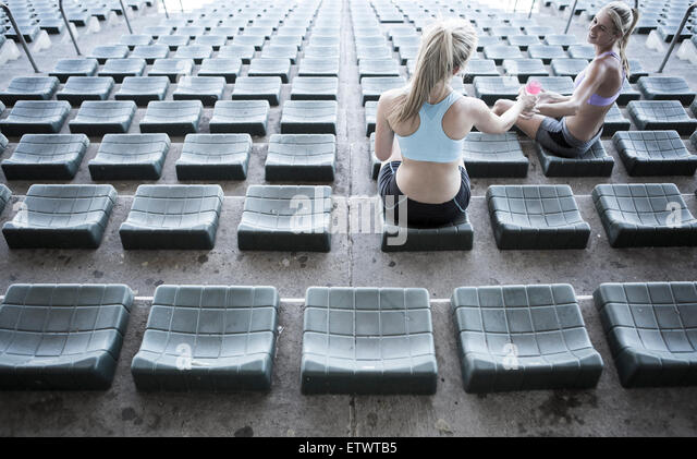 Two sportswomen sitting on grandstand of a stadium - Stock-Bilder