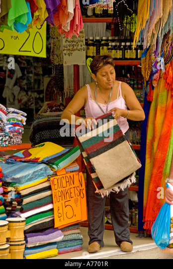 Mexico Cozumel San Miguel small store shop keeper with blankets - Stock Image