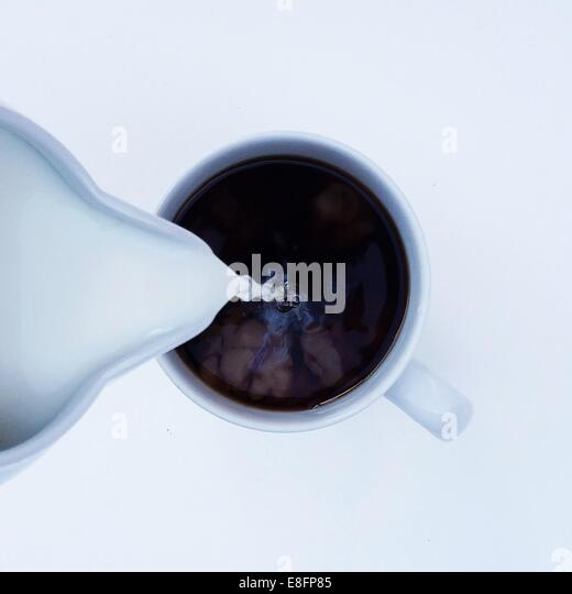Overhead view of milk being poured into cup of coffee - Stock Image