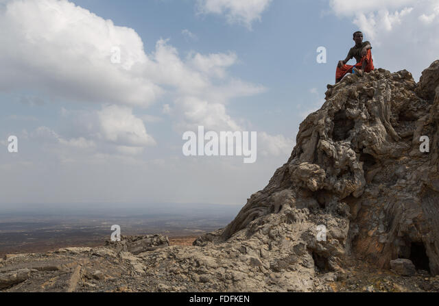 One of the local militia sits on top of an old Hornito in Erta Ale's caldera - Stock Image
