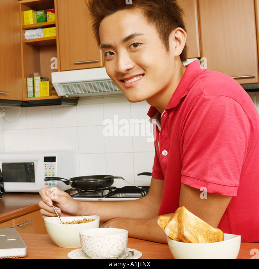 Portrait of a young man having breakfast in front of a laptop at a kitchen counter - Stock-Bilder