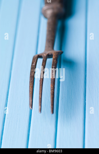 Old fashioned fork rusted over a blue wooden background - Stock-Bilder