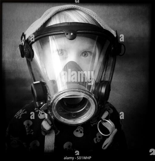 Young boy wearing a firefighter mask - Stock Image