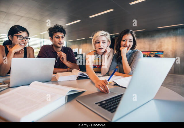 College students using laptop while sitting at table. Group study for school assignment. - Stock Image