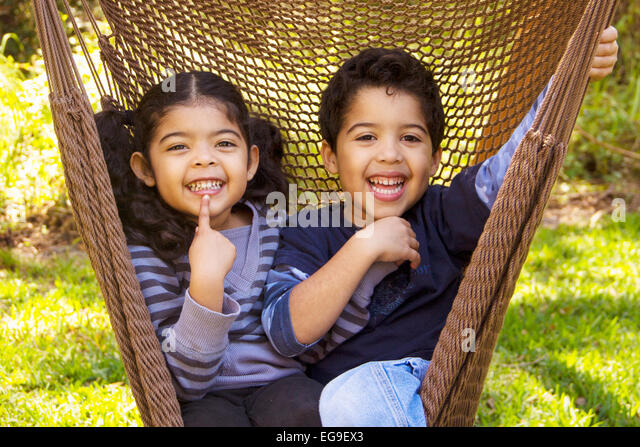 Twin brother and sister sitting in a hammock pulling funny faces - Stock Image