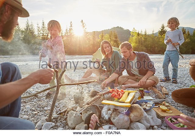 Family sitting around campfire cooking food on barbecue - Stock Image