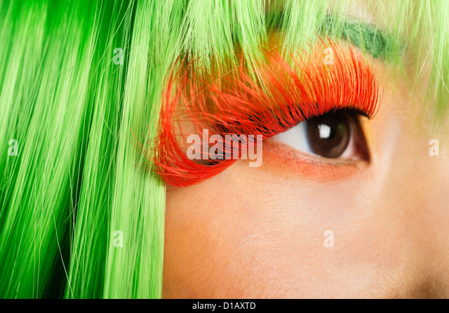 Extreme young woman's face false eyelashes green wig - Stock Image