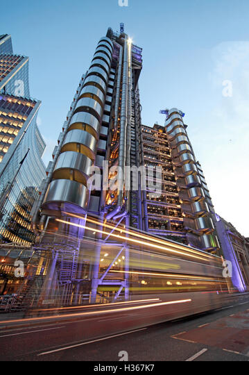 Traffic passes Lloyd's building London at dusk, Lime St, England - Stock Image