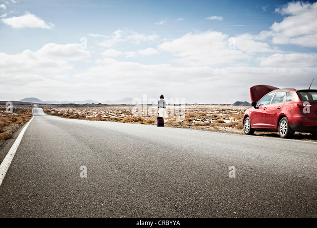 Woman with broken down car on rural road - Stock Image