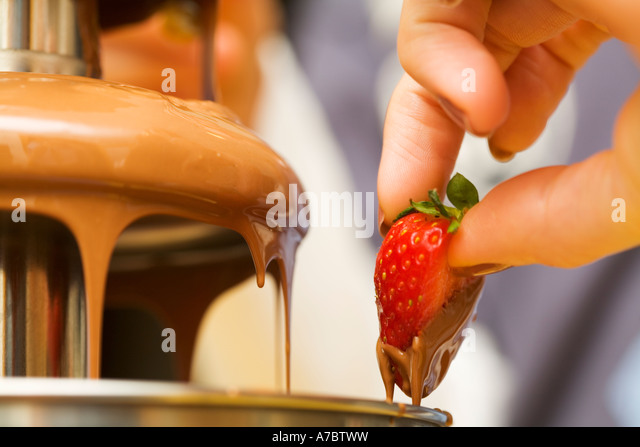 Hand dipping fresh strawberry into melted hot chocolate fountain - Stock Image