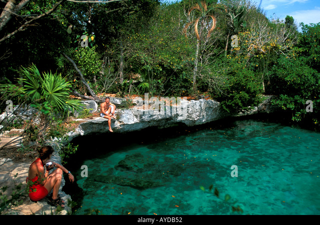 Mexico Yucatan Cancun area Xel-Ha water park couple sitting on limestone rocks - Stock Image