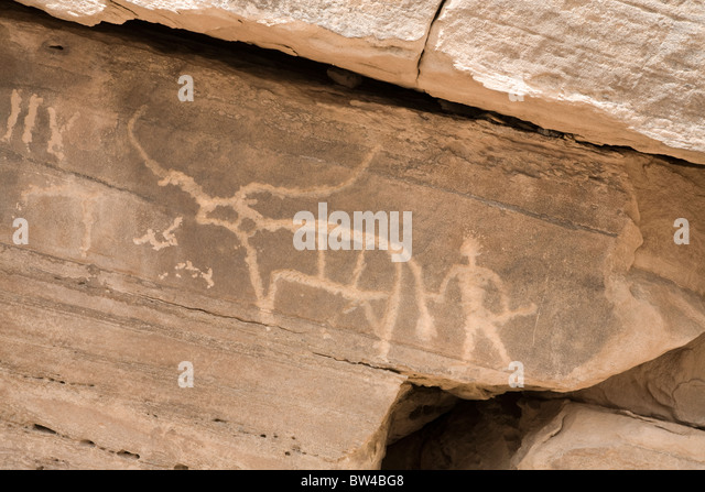 Petroglyph of man with stick holding tail of bull with large horns, Eastern Desert Egypt - Stock Image