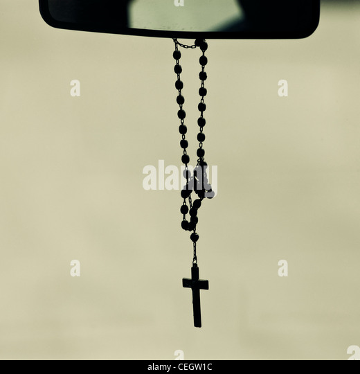 Crucifix hanging from mirror in a car - Stock-Bilder