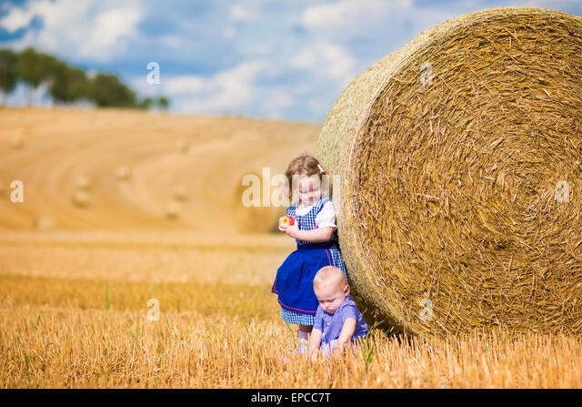 Two children, funny curly toddler girl and a little baby boy, wearing traditional German costumes playing in a field - Stock Image