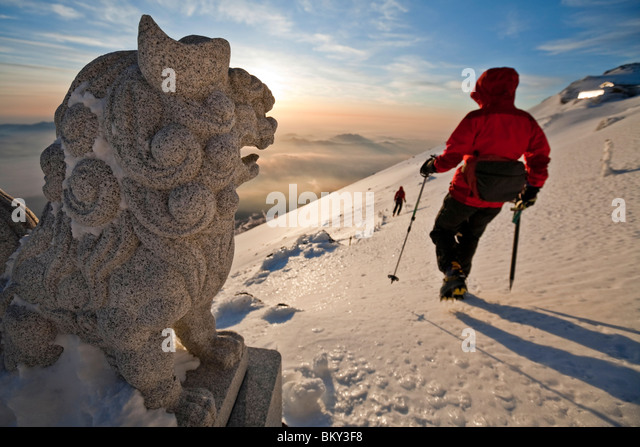 Two climbers are beginning a descent from the summit rim of Mount Fuji, Honshu, Japan. - Stock Image