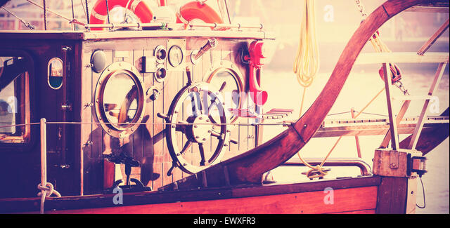 Retro vintage filtered photo of old sailing boat bridge with wooden steering wheel. - Stock Image