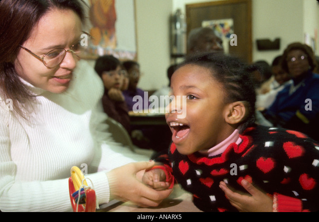 New Jersey East Orange Cerebral Palsy Center disabled student Hispanic therapist Black girl - Stock Image