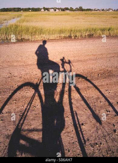 A shadow of a man on a bicycle on a dirt track in New England, USA. - Stock-Bilder