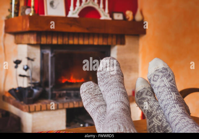 feet of couple near cozy fireplace in winter, family at home near fire - Stock Image