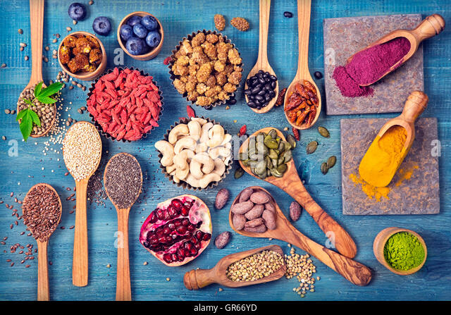 Super foods in spoons and bowls on a wooden background - Stock Image