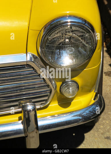 Closeup of metal and lights on a bright yellow mini car. - Stock Image
