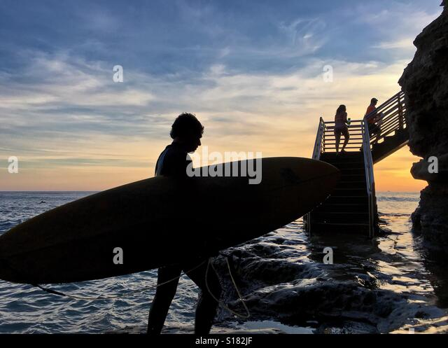 Silhouette of a surfer hold a surfboard along rugged coastline. Dusk at Sunset Cliffs Natural Park, Point Loma, - Stock-Bilder
