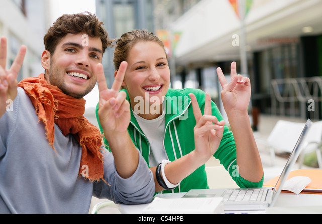 Portrait of friends gesturing peace while using laptop - Stock-Bilder