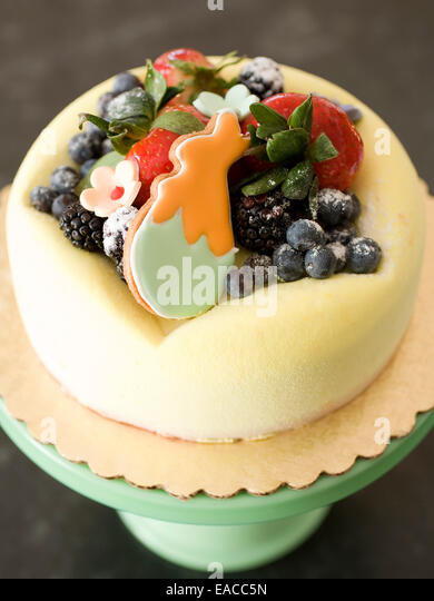 cake for Easter with fresh fruit and rabbit cookie - Stock Image