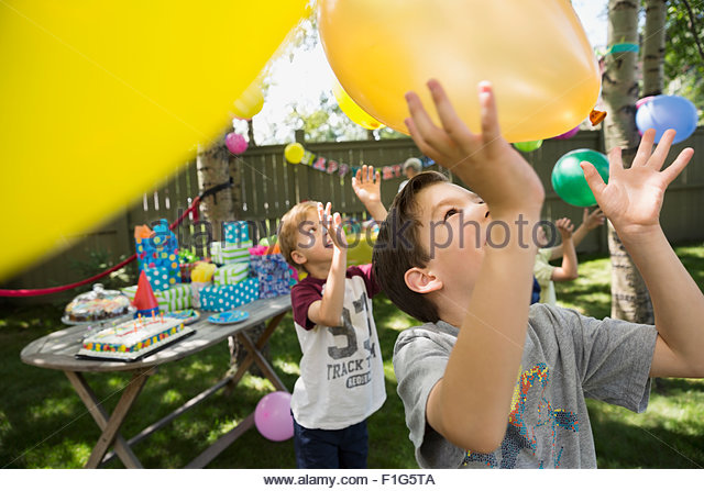 Boys playing with balloons at backyard birthday party - Stock Image