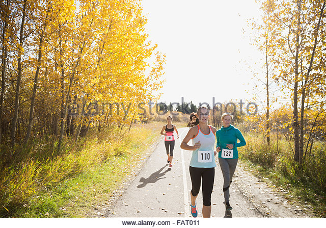 Runners racing on sunny autumn path - Stock Image