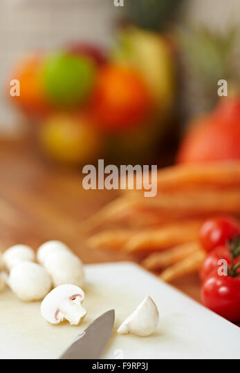 Knife on a kitchen counter cutting White Mushrooms in half - Stock Image