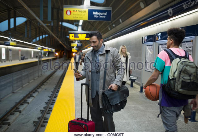 Businessman suitcase checking cell phone subway station platform - Stock Image