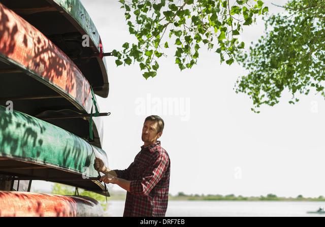 Colorado USA man stacking rowing boats lashing onto trailer - Stock Image